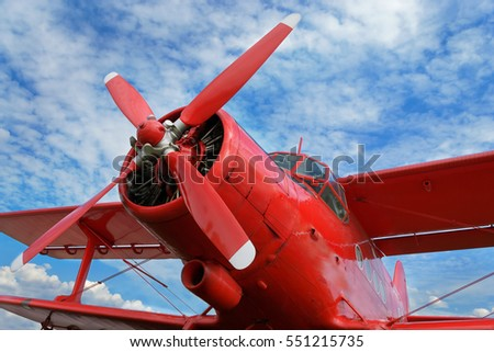 Close up view of red airplane biplane with piston engine and propeller on the cloudy sky background