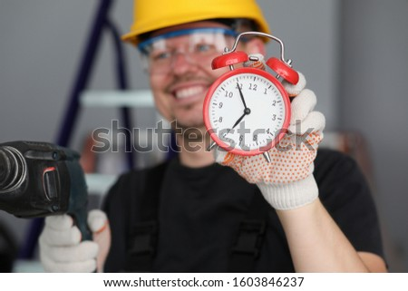 Close-up view of red clock showing seven morning. Cheerful builder holding drill and wearing bright yellow helmet and protective gloves with eyewear. Foreman concept