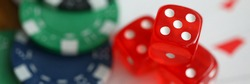 Close-up view of red dice laying on table. Macro shot of colourful casino chips on playing cards. Gambling and entertainment concept. Poker and games of chance