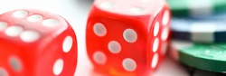 Close-up view of red glass dice cubes on playing cards. Colourful casino chips on table. Risk and luck. Poker and games of chance. Gambling and entertainment concept