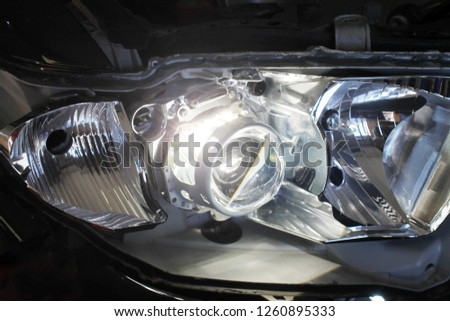 Close up view of repairing, installation and tuning headlight of modern automobile and car projector lens. Vehicle head xenon lamp in details. Concept of auto detailing, light and LED technology #1260895333