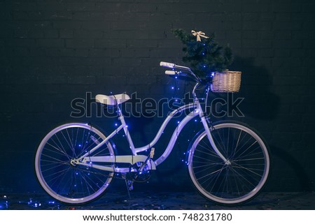 close up view of retro bicycle in christmas lights with christmas tree in basket against black brick wall
