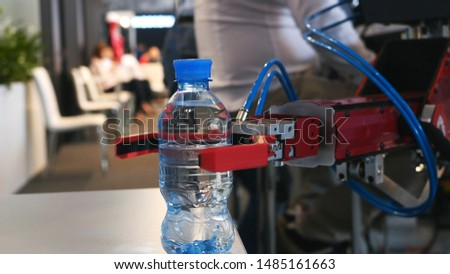 Close-up view of robotic hand holding and relocating a bottle with water on the exhibition. Media. Different working robots collection presented on the robotics forum exhibition