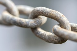 Close up view of rusty metal chain links on a gray background