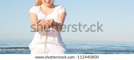 Close up view of sand filtering through a young girl's hands while sitting down on a beach with the sea in the background, smiling.