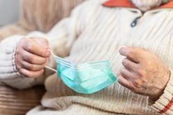 Close up view, of Senior man hands putting face mask against coronavirus .