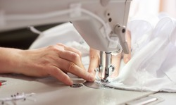 Close up view of sewing process. Female hands stitching white fabric on professional manufacturing machine at workplace. Seamstress hands holding textile for dress production. Light blurred background