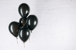 close-up view of shiny black balloons on white
