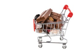 Close up view of shopping cart filled with candies and chocolate. Unhealthy food. Health concept.
