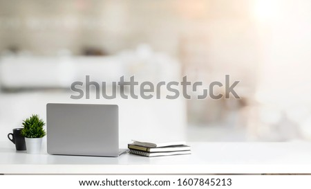 Close up view of simple workspace with laptop, notebooks, coffee cup and tree pot on white table with blurred office room background