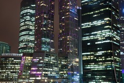 Close up view of skyscrapers at night, office centers in downtown financial district in megapolis, bright lights of hundreds windows, luxury modern property for business, high-rise towers background