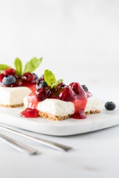 Close up view of slices of cherry cheesecake garnished with cherries, blueberries and mint.