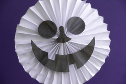 Close up view of smiling skull face decoration made from folded white paper on the purple background. Theme of handmade decorations for Halloween.