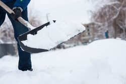 close up view of snow shovel with snow in man's hands. Man clean backyard of his house after blizzard. Spring snow cleaning.