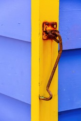 Close up view of some of the weathered blue and yellow painted boards with a rusted cabin door hook, all part of the iconic bathing boxes on Brighton Beach, Brighton, VIC, Australia