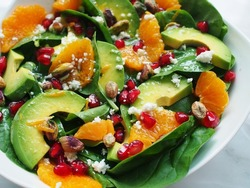 close up view of spinach, avocado salad with orange, pomegranate and pistachio in white bowl on marble background