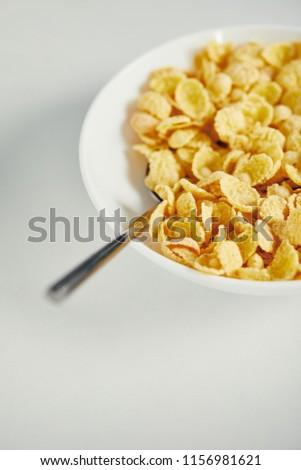 close up view of spoon and corn flakes with milk in bowl for breakfast on white surface #1156981621
