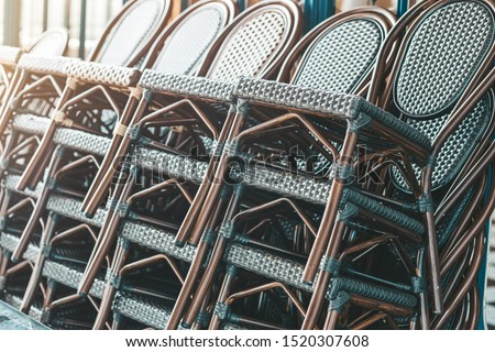 Close up view of stacked rattan outdoor armchairs. Horizontal shot