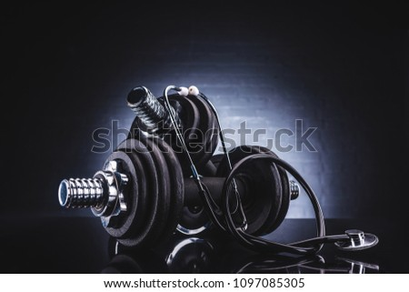close-up view of stethoscope and dumbbells, healthy lifestyle concept