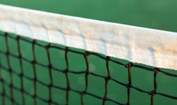 Close up view of tennis court through the net