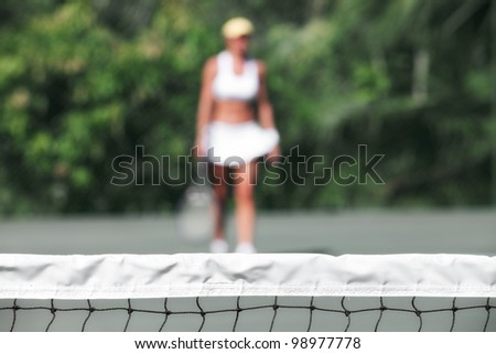 close up view of tennis net with player on the back. focused on the net