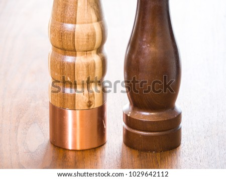 Close up view of the bottom half of a carved wood salt and pepper grinder container or kitchen tools with rounded shapes sitting on a dark wood grain table.