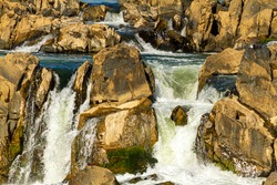 Close up view of the cascading water at great falls region of the potomac river. Image was taken from a scenic overlook at Great Falls park in virginia. Water sparkles as it moves fast throug rocks.