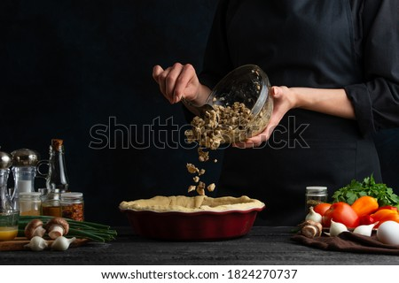 Close-up view of the chef adds mushrooms to the pie. Dark background. Cooking at the professional restaurant or hotel kitchen. Background of preparing homemade pie. Bakery concept. Foto stock ©