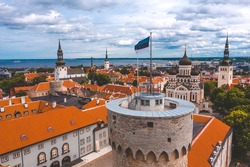 Close up view of the Estonian flag on top of the old medieval tower.