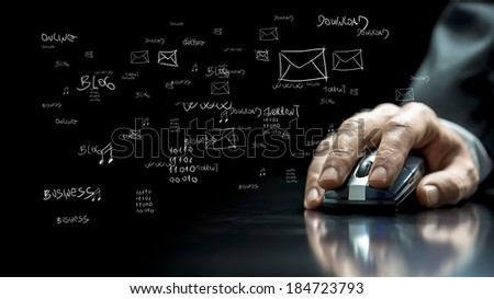 Close up view of the hand of a businessman using a computer mouse on a reflective black surface with hand-drawn notations and computer icons on the dark background.