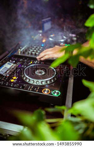 Close up view of the hands of a male disc jockey mixing music on his deck with his hands poised over the vinyl record on the turntable and the control switches at night
