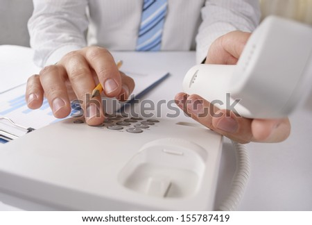Close up view of the hands of a man making a telephone call on a landline holding the handset close to the camera and dialling in the number on the keypad with the other hand
