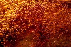 Close up view of the ice cubes in dark cola background. Texture of cooling sweet summer's drink with foam and macro bubbles on the glass wall. Fizzing or floating up to top of surface