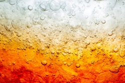 Close up view of the ice cubes in dark cola background. Texture of cooling sweet summer's drink with foam and macro bubbles on the glass wall. Fizzing or floating up to top of surface.