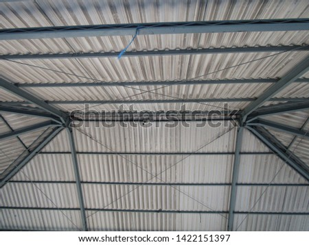 close up view of the pyramid triangular roof frame with grey color asbestos tile asphalt concrete metal clay policarbonat glass with green iron steel skeleton. Construction home hall built structure #1422151397