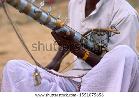Close-up view of the Ravanhatta, a stringed musical instrument of ancient origin used by Indian street musicians. The Bhopa caste man perform a melancholic song at Puskar Camel Fair (Rajasthan-India) #1551075656