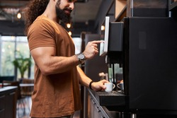 Close up view of the startup coworker man making coffee during office break time while standing near the coffee machine and pushing at the button with his finger
