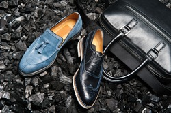 Close-up view of the stylish and elegant black leather men's dress shoes and a bag for business meetings.