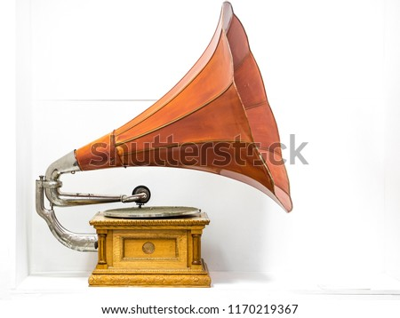 Close up view of the vintage musical gramophone with yellow body and red horn and  on a white background #1170219367