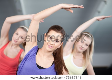 Close up view of three beautiful young woman doing aerobics exercises