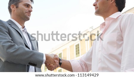 Close up view of two businessmen shaking hands while standing in front of a classic European building, outdoors.