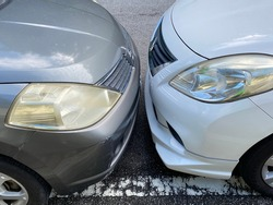 Close up view of two cars parking bumper to bumper very near each other head on