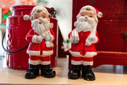 Close up view of two porcelain Santa Claus Dolls on a wooden table. Decorative dolls stand in front of a vintage chest of drawers and an ornamental jar. A Good concept for Christmas, New Year themes.