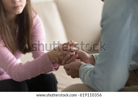 Close up view of upset couple, guy holding hands of crying woman, trying to comfort and console her, boyfriend apologizing offended lady, asking for forgiveness. Support, regret and compassion