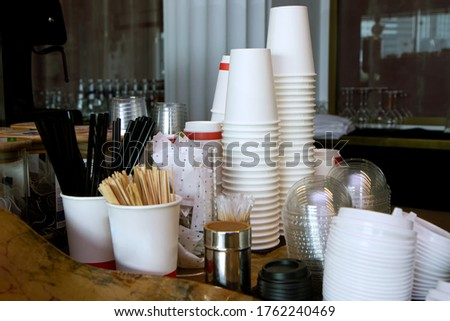 Close-up view of various disposable wooden sticks, wooden spoon, tooth sticks, cup covers, Take away boxes, napkins and sugar bags on wooden counter in cafe for self-service and take away drinks Photo stock ©