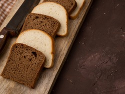close-up view of white and black bread slices with knife on wooden surface and maroon background with copy space