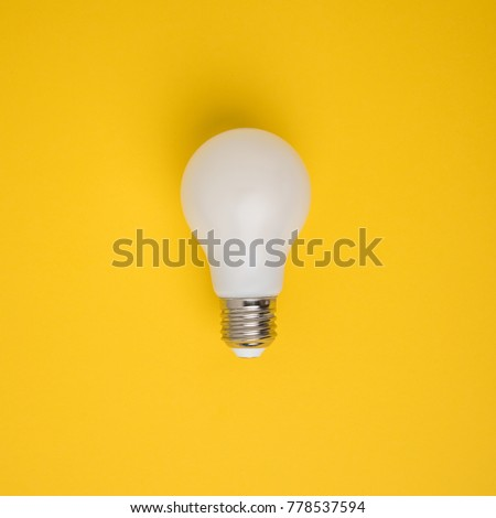 Stock Photo close up view of white light bulb isolated on yellow
