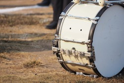 Close-up view of white orchestral drum and silver parts laying on the brown lawn in the sports day parade