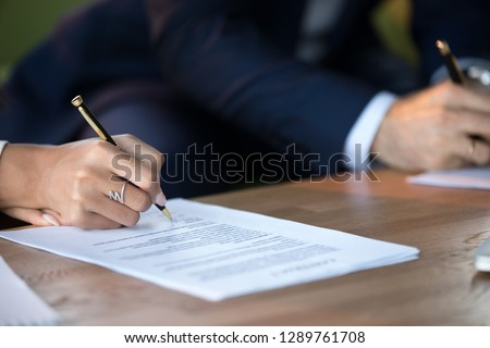 Close up view of woman and man signing document concluding contract concept making prenuptial agreement visiting lawyer office, female and male partners or spouses writing signature on decree paper Photo stock ©