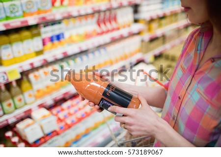 Close up view of woman choosing a bottle of fruits juice at supermarket